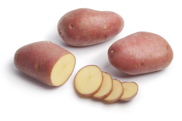 Whole and sliced Roseval potatoes on white background